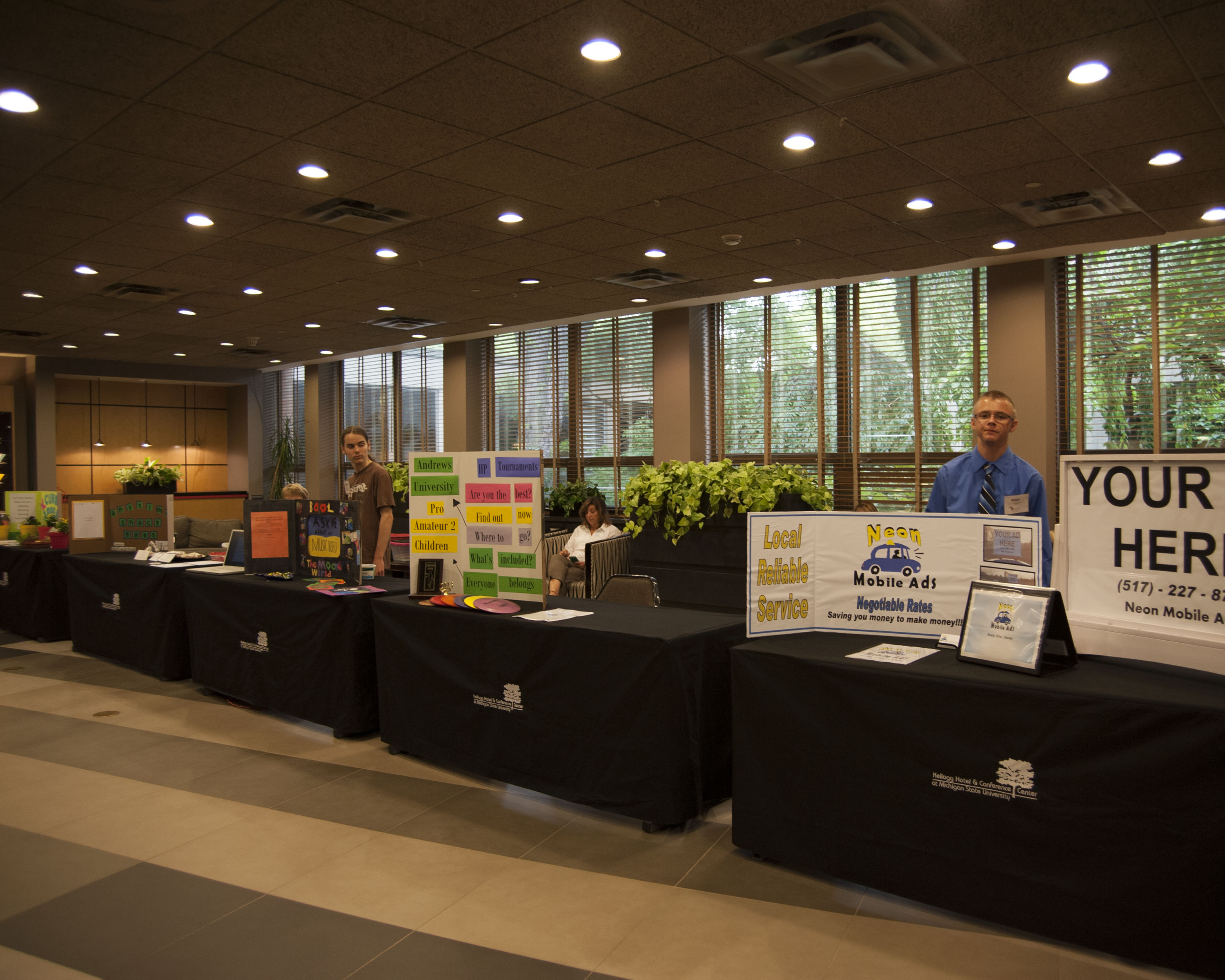 Photo of young entrepreneurs promoting their businesses at the Innovate Michigan! Summit on September 4, 2014.