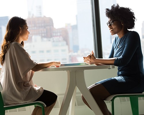 Two women talking at a table